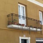 Balcón construido con barrotes combinadas de culebrines y bastones lisos         En este modelo de barandilla, esta rematado con una cenefa de estilo clásico