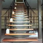 Escalera de hierro construida sobre una sola zanca central         Los escalones de madera descansando sobre soportes de chapa de hierro       plegadas. La barandilla se ha fijado al lateral de los peldaños