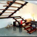 Escaleras para ambientes interiores construida en dos tramos sin barandillas        La estructura de hierro pintado negro mate, incorpora un soporte para anclar          los peldaños de madera de forma discreta dando transparencia al ambiente