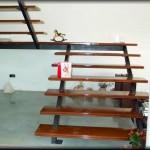 Escaleras para ambientes interiores construida en dos tramos sin barandillas         La estructura de hierro pintado en negro mate, integra las piezas de madera        dándole al conjunto una transparencia y no recarga la estructura del ambiente